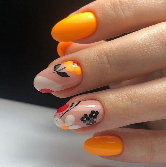 Pomarańczowe paznokcie z wzorkami kwiatów